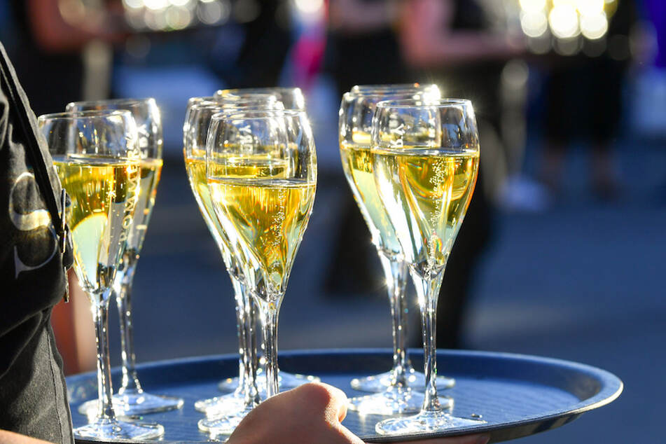 """Eine Frau hält Gläser mit Champagner. Weil ein """"Champagner Sorbet"""" nicht nach dem französischen Schaumwein schmeckte, gingen Hersteller gegen die Bezeichnung von Aldi vor. (Symbolbild)"""