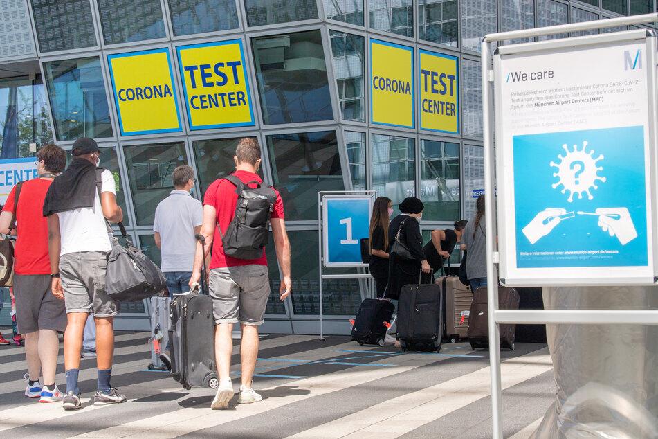 Reisende gehen zur Registration des Corona-Testzentrum am Münchner Flughafen.