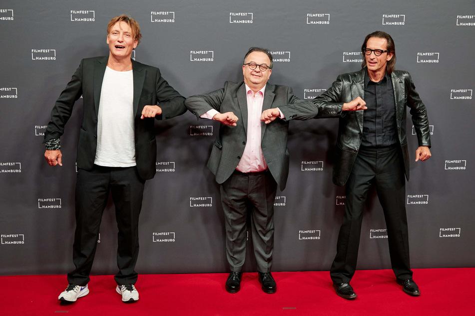 Oliver Masucci (l.-r.), Schauspieler, Albert Wiederspiel, Leiter des Filmfestes, und Oskar Roehler, Regisseur, stehen auf dem Roten Teppich zur Eröffnung des Filmfestes Hamburg.
