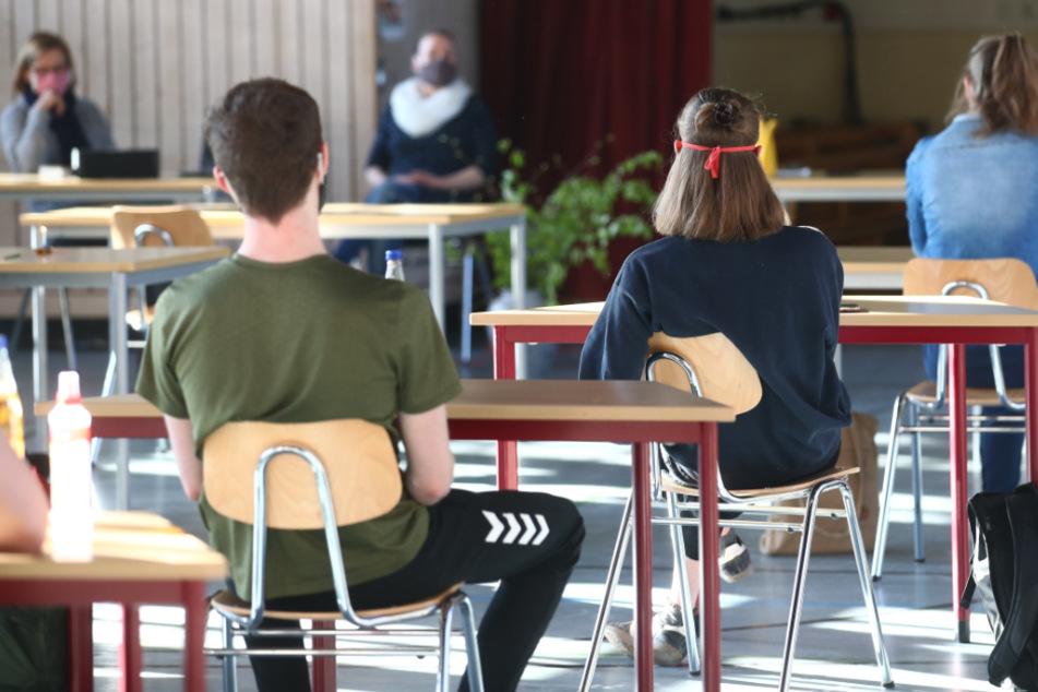 Schüler mit Mundschutz sitzen bei der Prüfungsvorbereitung fürs Abitur in einer zum Schulraum umfunktionierten Turnhalle.