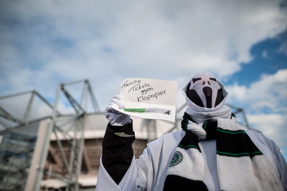 Ein Fan in einem Geisterkostüm steht vor dem Stadion mit einem Zettel auf dem «Tausche Tickets gegen Klopapier» steht.