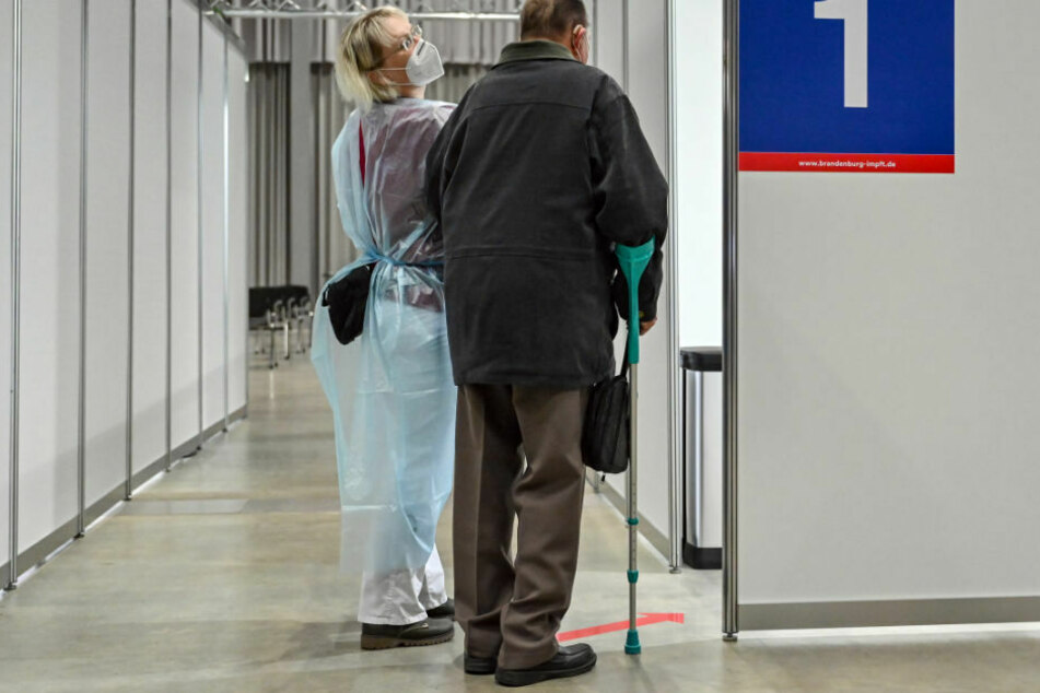 Ein älterer Mann wird zur Corona-Schutzimpfung in eine Kabine im Impfzentrum Frankfurt (Oder) geführt.