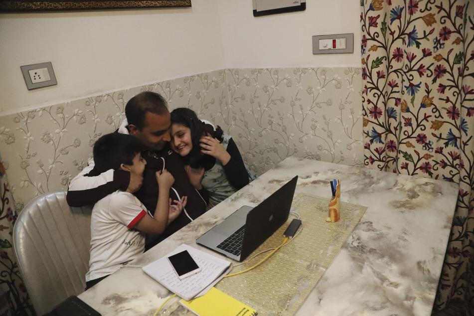 """Srinagar: Der Associated-Press-Fotograf Mukhtar Khan (M) feiert in seinem Haus und umarmt seine Kinder Mohammad Zehran (l) und Tazkiya, nach der Bekanntgabe der Pulitzer-Preise. Er ist einer von drei AP-Fotografen, die für ihre Berichterstattung über den Konflikt in Kaschmir und im indischen Jammu den Pulitzer-Preis in der Kategorie """"Feature-Fotografie"""" gewonnen haben."""