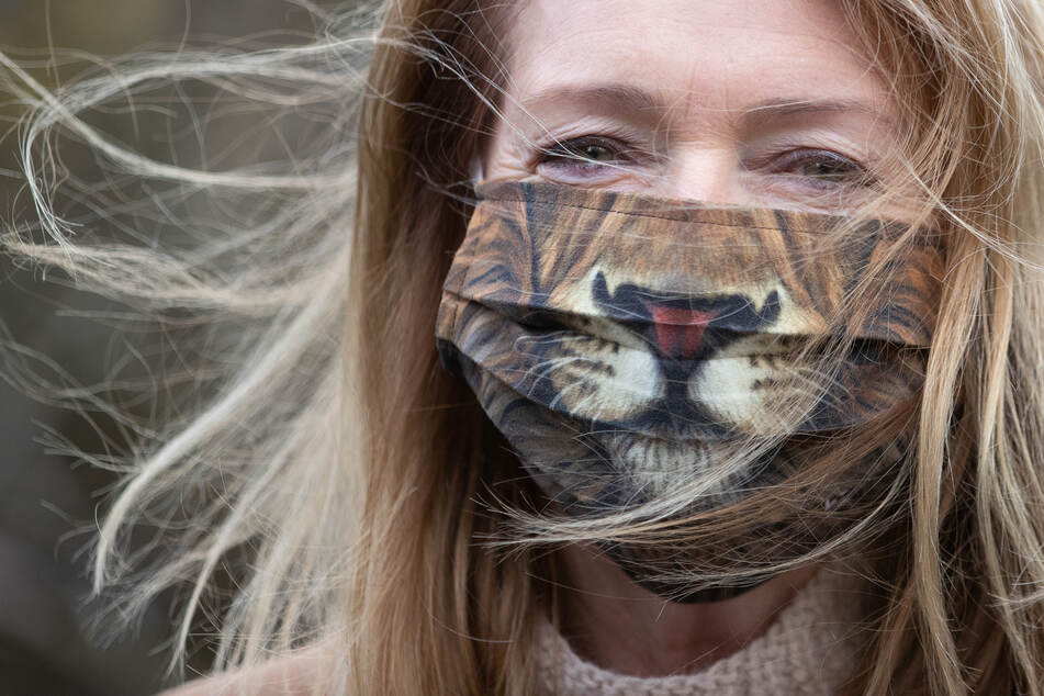 Niedersachsen, Osnabrück: Eine Frau trägt einen Mund-Nasen-Schutz mit einem Tiger-Motiv.
