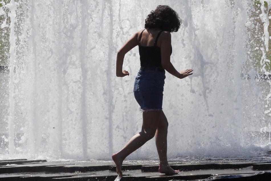 Eine junge Frau sucht etwas Abkühlung an einem City-Brunnen im Lustgarten.
