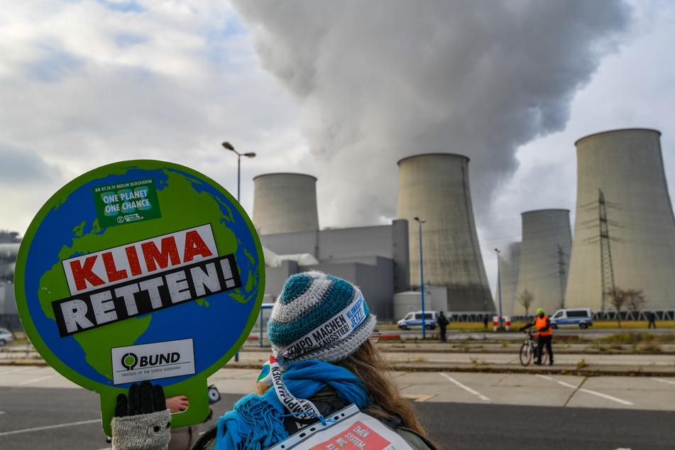 Eine Umweltschutzaktivistin demonstriert vor den Türmen des Braunkohlekraftwerks Jänschwalde.