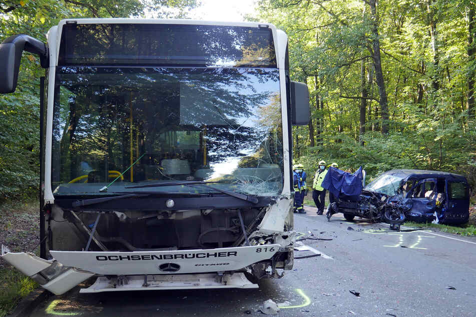 Rettungskräfte stehen neben einem zerstörten Auto. Eine Rentnerin (77) war damit frontal in einen Linienbus gekracht und noch am Unfallort verstorben.