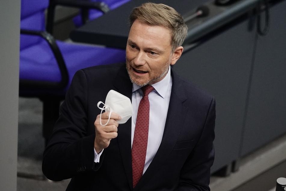 Christian Lindner (42), Fraktionsvorsitzender und Parteivorsitzender der FDP, zeigt seine FFP2 Maske in der Debatte zu Corona-Impfungen im Bundestag.