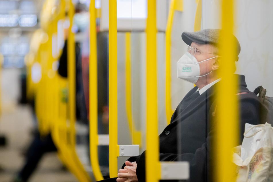 Ein Mann sitzt mit FFP2-Maske in der U-Bahn.