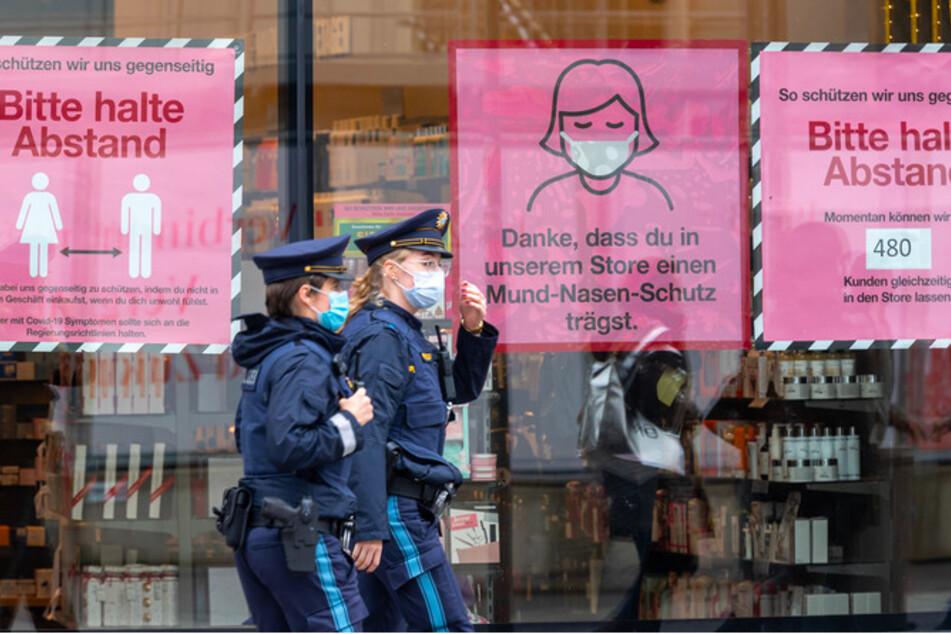 Polizistinnen gehen an einem Schaufenster in der Münchner Innenstadt vorbei.