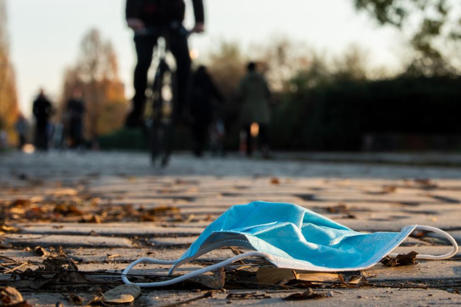 Auf einem Gehweg im Mauerpark Berlin liegt eine Mund-Nasen-Bedeckung auf dem Boden. (Symbolbild)