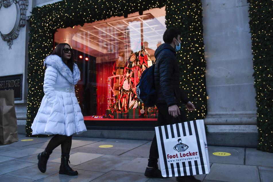 Passanten gehen an einem weihnachtlich dekorierten Schaufenster bei Selfridges in der Oxford Street vorbei. Ab diesem Donnerstag, den 05.11.2020, gilt in England zur Bekämpfung der Corona-Pandemie ein Teil-Lockdown.