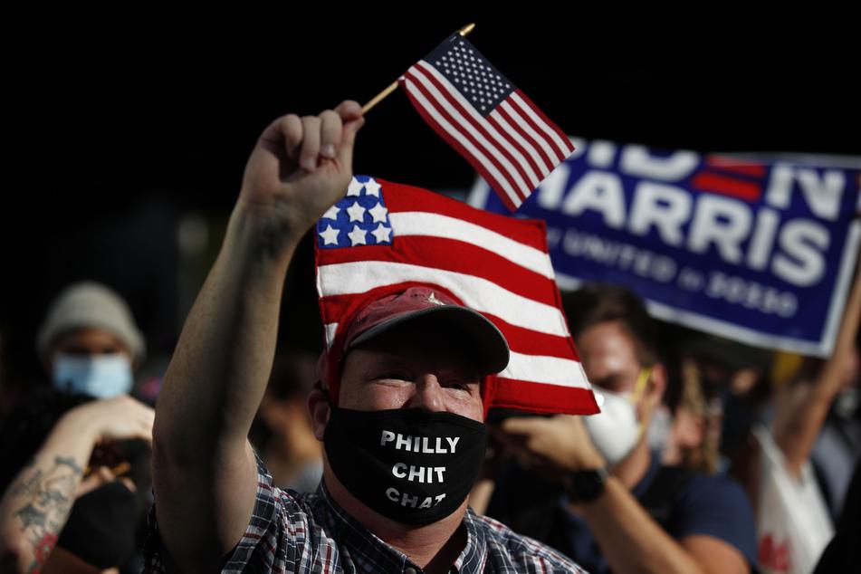 Die Menschen feiern vor dem Pennsylvania Convention Center in Philadelphia mit Mund-Nasen-Schutz. Biden besiegte am Samstag Präsident Trump und wird damit der 46. Präsident der Vereinigten Staaten.