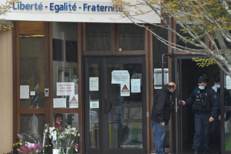 Die französische CRS-Polizei (Compagnies Republicaines de Securite) verlässt eine Mittelschule in Conflans Saint-Honorine, 30 km nordwestlich von Paris, neben Blumen, die nach einer brutalen Messerattacke ausgestellt wurden