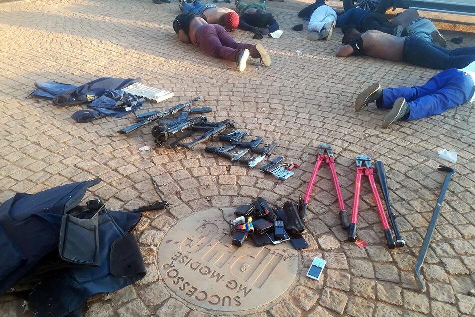Tatverdächtige liegen neben konsfizierten Schusswaffen und Munition auf dem Boden.