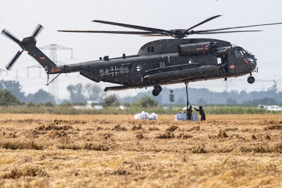 Ein Transporthubschrauber CH-53 der Bundeswehr nimmt am vergangenen Donnerstag sogenannte Big-Bags auf, um sie in den Ortsteil Blessem zu fliegen. Die mit Kies befüllten Plastiksäcke sollen in die Erft gesetzt werden, um dort das Wasser anzustauen.