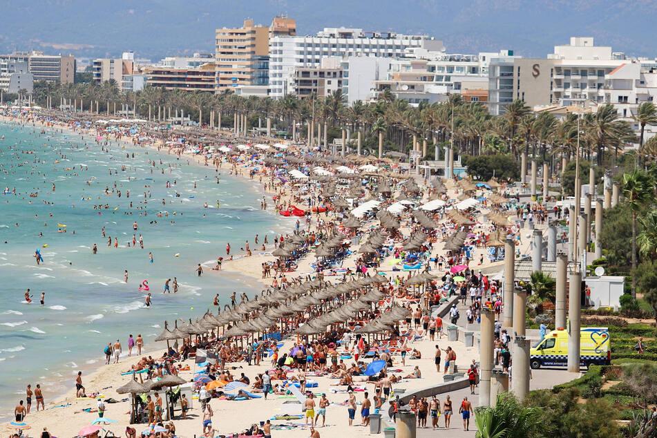 Touristen sonnen sich am Strand von El Arenal auf der Balearen-Insel Mallorca. Im Sommer 2020 dürfte es dort wohl leerer aussehen.