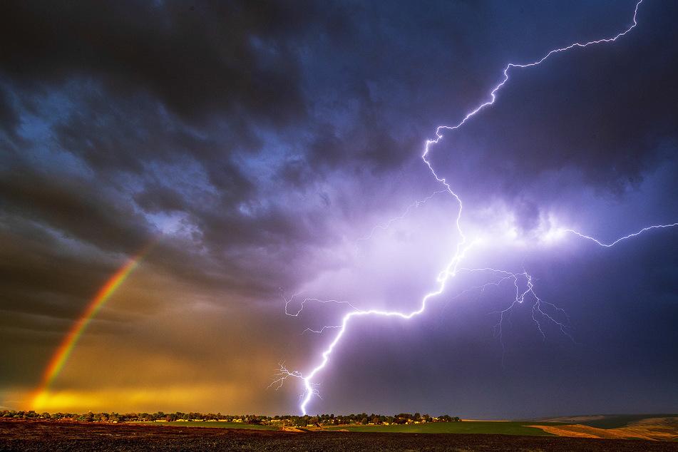 Ein Blitz schlägt in der Nähe eines Regenbogens ein, während es stark gewittert.