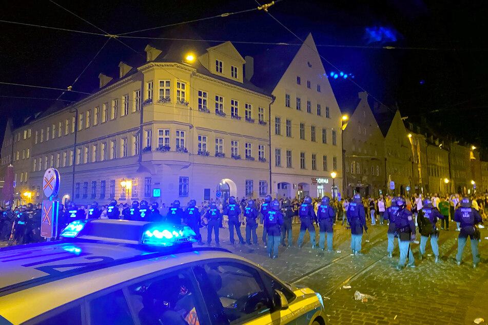 Polizisten stehen an einem Platz in der Innenstadt, wo sich Menschen zum Feiern versammelt haben.