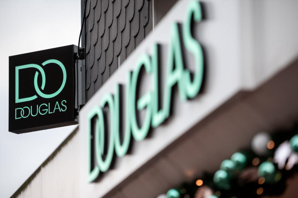 Der Schriftzug mit dem aktuellen Logo der Firma Douglas hängt an einer Außenwand.