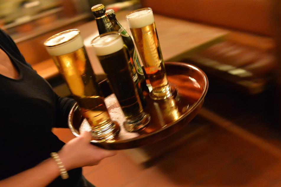 Eine Bedienung trägt in einem Lokal ein Tablett mit Bier. Wer nur einen Corona-Test hat, darf beim 2G-Modell nicht in die Kneipe. (Symbolbild)