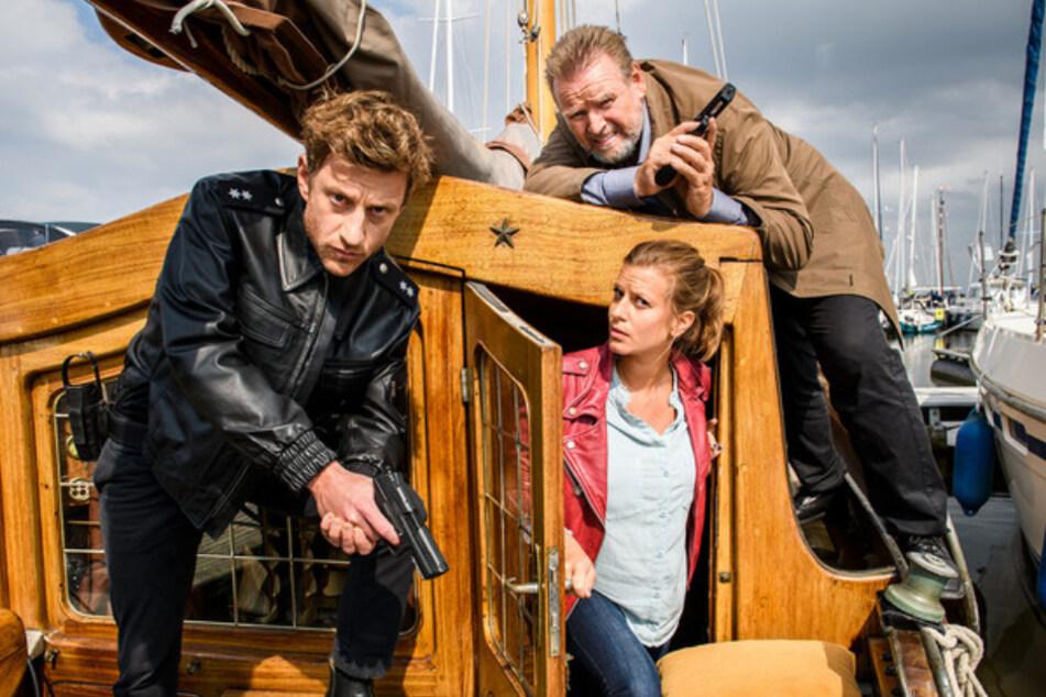 Henk Cassens (Maxim Mehmet, l.), Insa Scherzinger (Theresa Underberg, M.) und Kommissar Brockhorst (Felix Vörtler, r.) stoßen auf einen Münsteraner Polizisten - das wird turbulent.