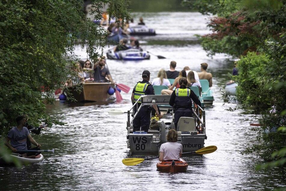 Wasserschutzpolizisten fahren mit einem Motorboot über den Mühlenkampkanal, auf dem viele Freizeitsportler unterwegs sind.