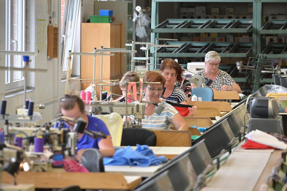 Fleißige Arbeiterinnen nähen Damen- und Herrenwäsche im Produktionssaal.
