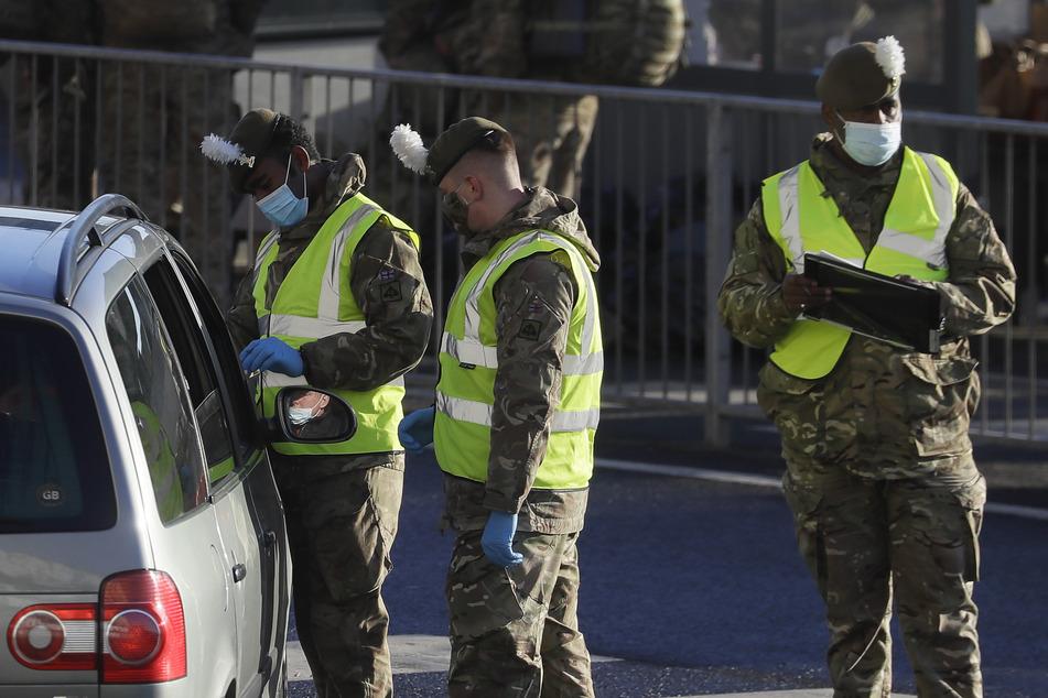Großbritannien, Dover: Soldaten führen Corona-Test bei einem Autofahrer vor dem Hafen von Dover durch.