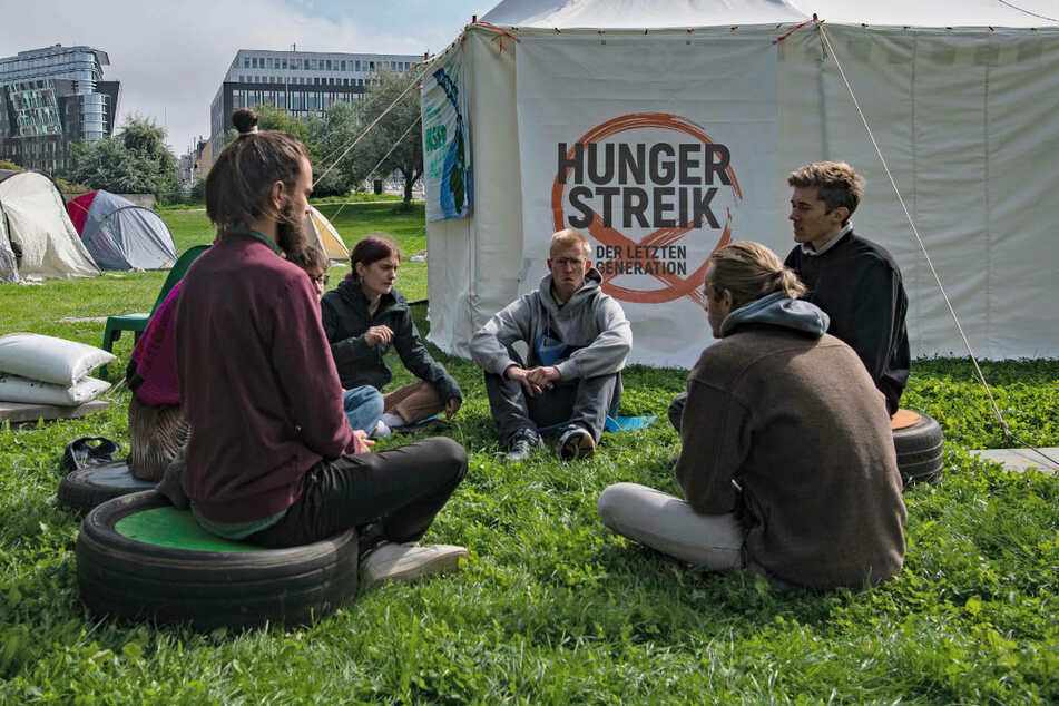 Umweltaktivisten sitzen im Regierungsviertel zusammen vor einem Zelt. Seit Tagen befinden sich die jungen Menschen in einem Hungerstreik für eine bessere Klimapolitik.