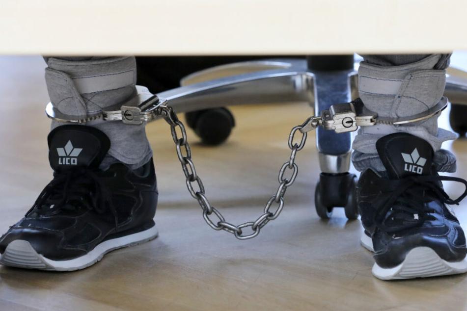 Der Angeklagte sitzt mit einer Fußfessel im Saal des Landgerichts. (Archivbild)