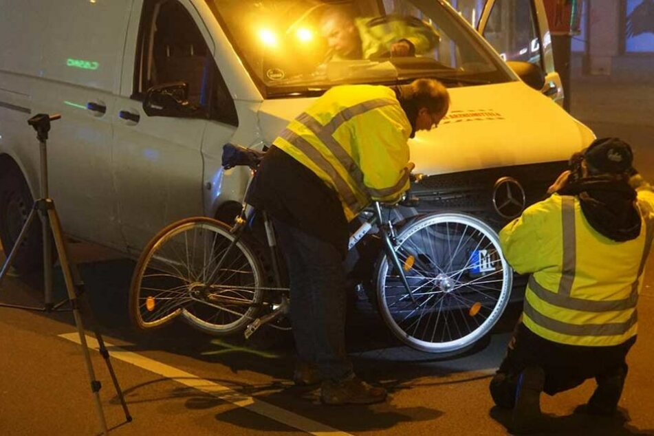 Unfallermittler halten das Fahrrad an die Aufprallstelle des Transporters.