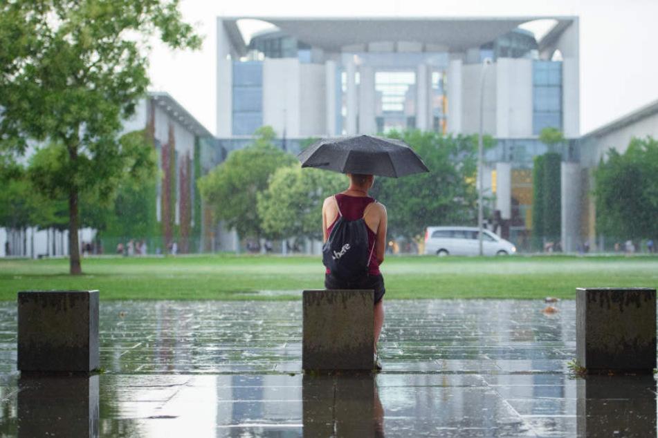 Eine Frau sitzt mit einem Regenschirm im Regen vor dem Bundeskanzleramt.