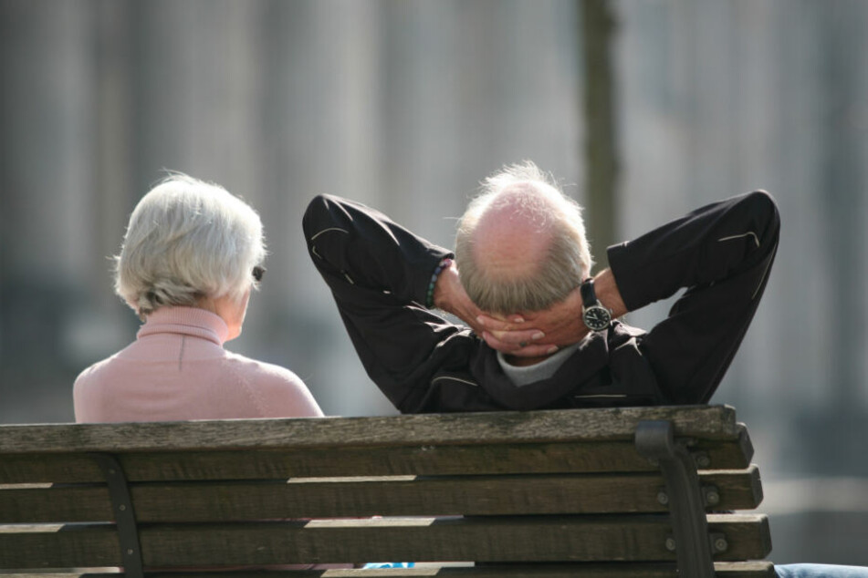 Ein Rentnerpaar sitzt auf einer Bank.