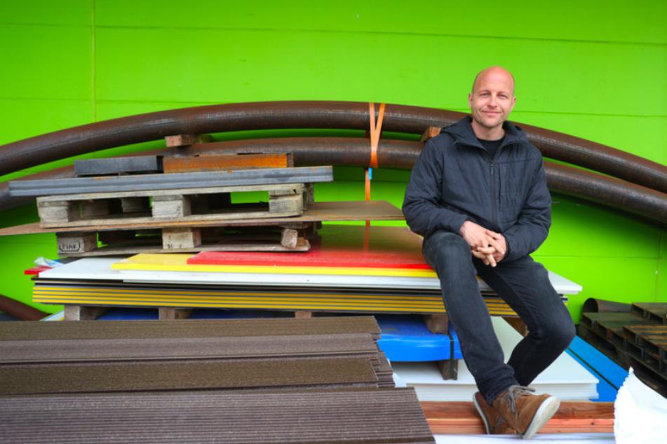 """Dirk Scheumann (42), Geschäftsführer des Pumptrack-Herstellers """"Schneestern"""" sitzt vor der Produktionshalle seiner Firma in Durach zwischen Baumaterialien."""