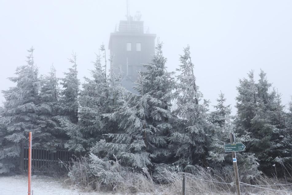Der Fichtelberg ist in eine winterliche Wolke und zarte Schneedecke gehüllt.