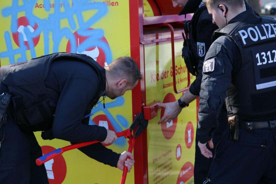 Polizisten brechen die Altkleidercontainer in der Umgebung auf.