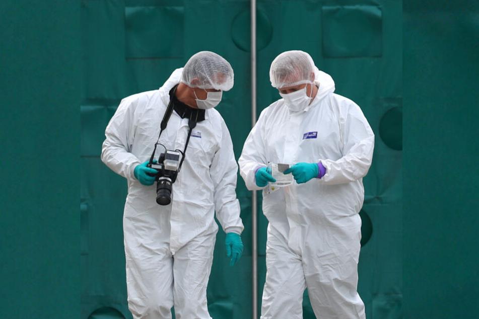 Mitarbeiter der Spurensicherung arbeiten in der Nähe des LKW-Containers, in dem 39 Leichen gefunden worden sind.