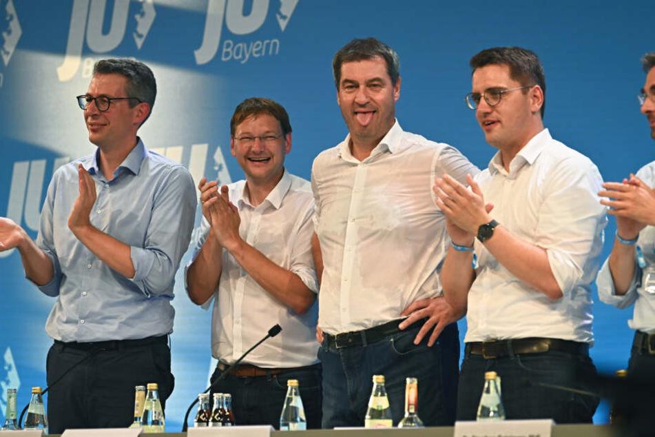 Markus Söder (CSU, M), Ministerpräsident von Bayern, steht nach seiner Rede mit durchgeschwitztem Hemd auf der Bühne und streckt aufgrund der warmen Temperaturen die Zunge heraus.