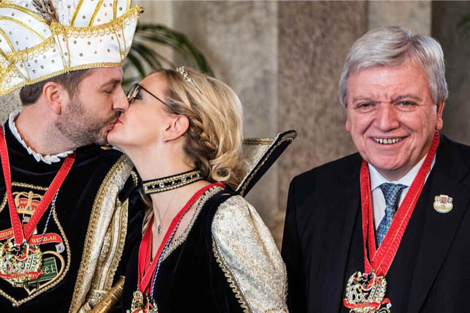 Mit Orden behängt lächelt Volker Bouffier (r.), während sich neben ihm ein Prinzenpaar küsst.
