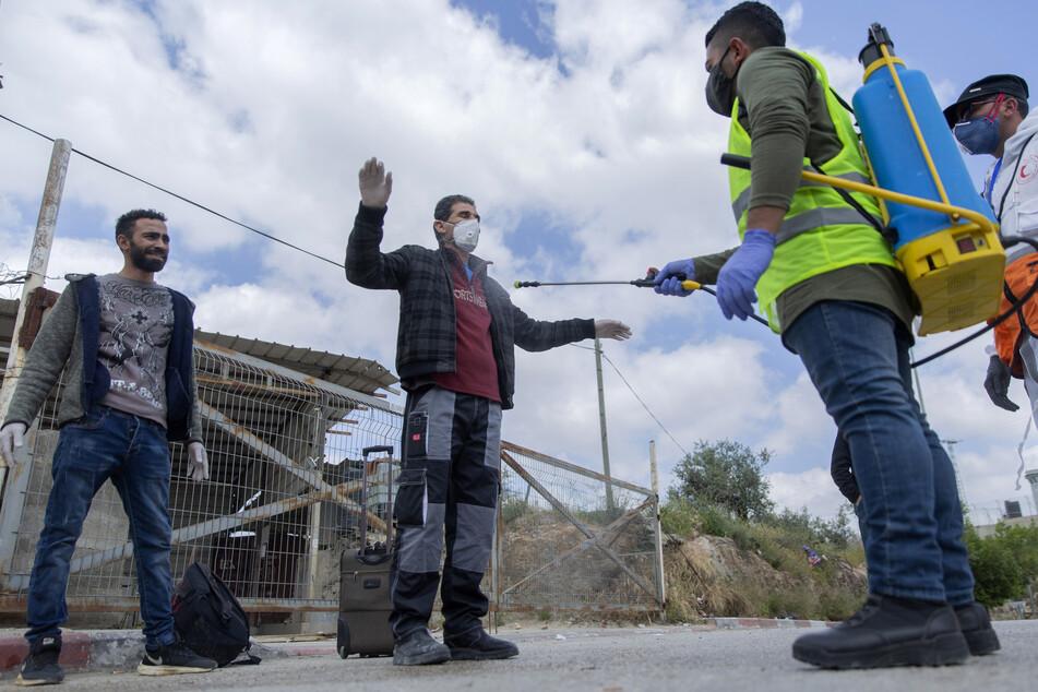 Ein Sanitäter des palästinensischen Gesundheitsministeriums desinfiziert palästinensische Arbeiter, als sie einen Kontrollpunkt der israelischen Armee verlassen.