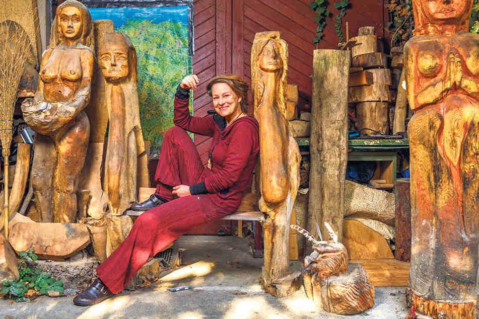 Julia Henke (51) gönnt sich auf ihrer selbst  gesägten Bank eine Verschnaufpause von der Holzarbeit.