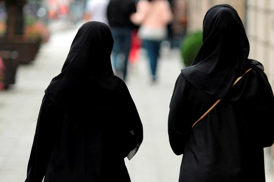 Zwei Frauen mit Burka schlendern durch die Straßen.