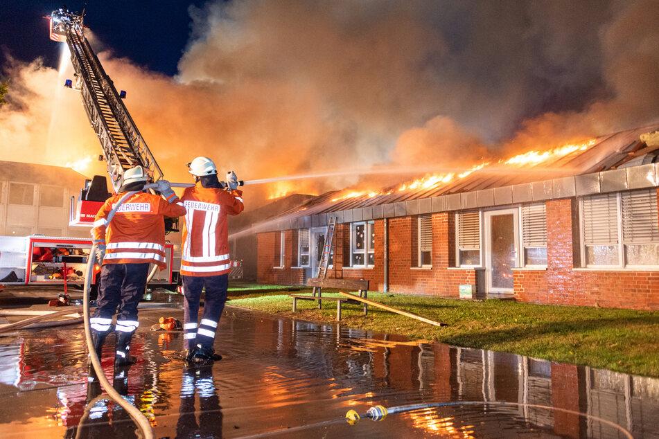 Einsatzkräfte der Feuerwehr kämpfen gegen die Flammen.
