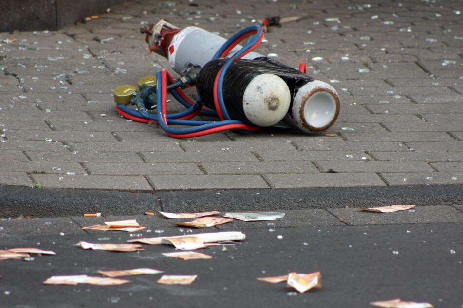 Geldscheine und Gasflaschen liegen auf der Straße vor der Commerzbank. Die Täter flüchteten.