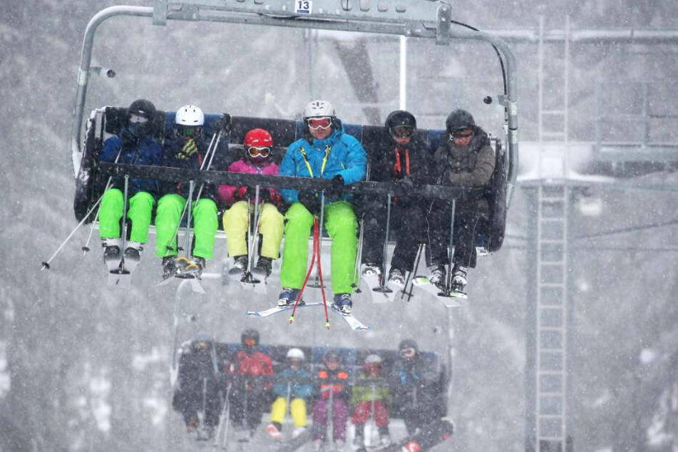Skifahrer sitzen in einem Skilift.