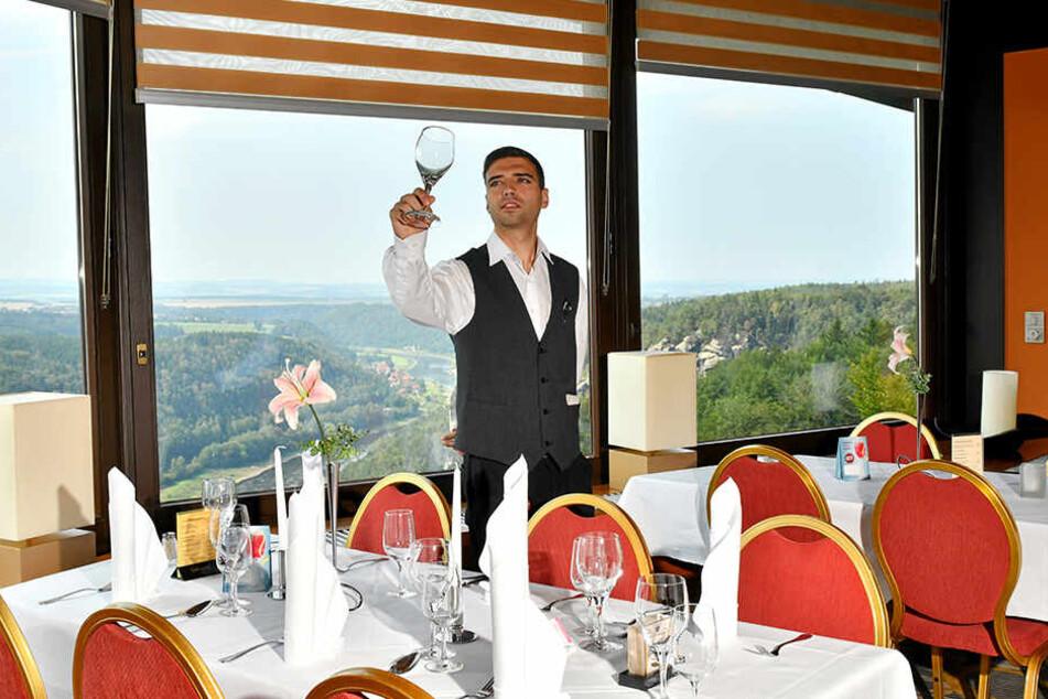 Kellner Javier Navarro Candil deckt die Tische mit der fantastischen Aussicht auf die Sächsischen Schweiz ein.