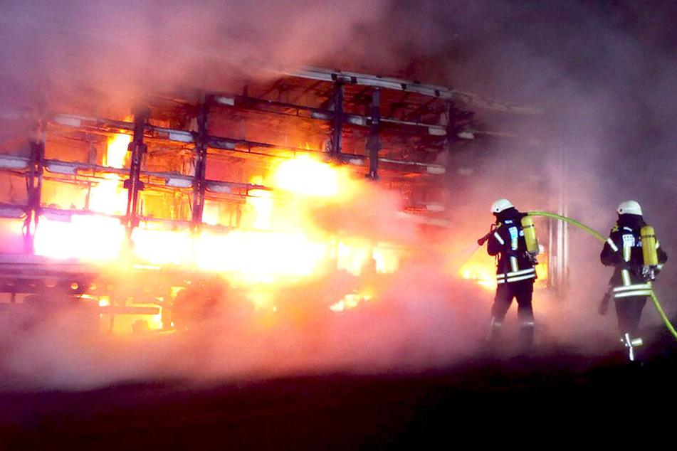 Feuerwehrleute löschen einen brennenden Laster auf der Autobahn.