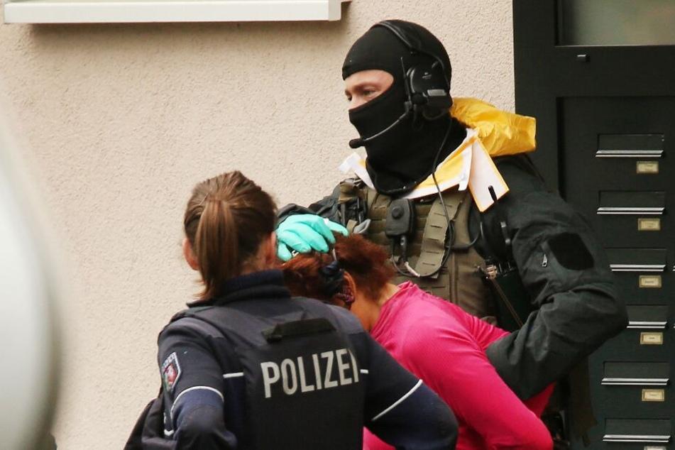 Die 50-jährige Frau wird von Polizisten aus dem Haus geführt.
