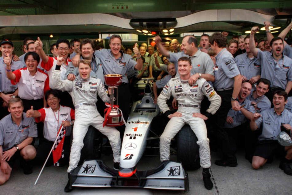 November 1998: Mika Hällinen (Mitte links) und David Coulthard (Mitte rechts) bejubeln mit McLaren-Mercedes-Team- und Motorsportchef Norbert Haug (hinter Häkkinen) den Titelgewinn im japanischen Suzuka.